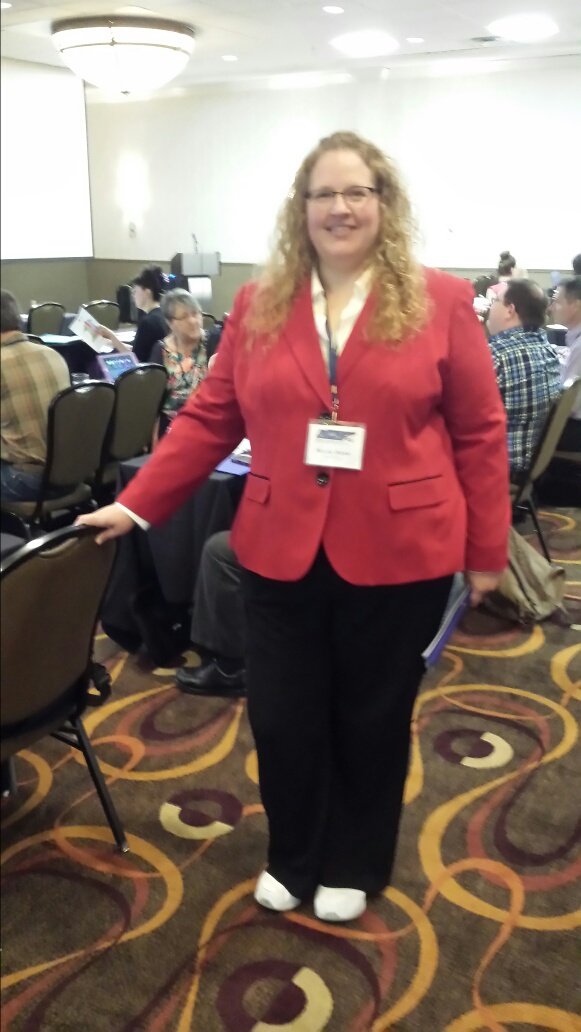 Nic in a red coat and black pants wearing a conference badge